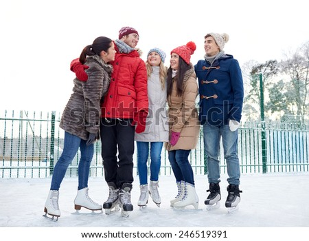 people, winter, friendship, sport and leisure concept - happy friends ice skating and hugging on rink outdoors - stock photo