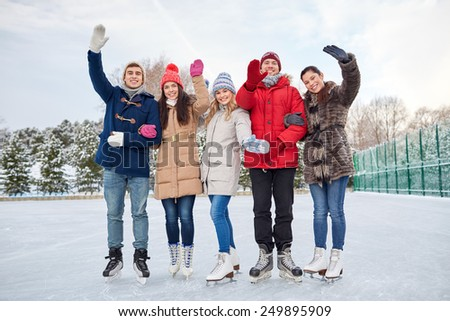 people, winter, friendship, sport and leisure concept - happy friends ice skating and waving hands on rink outdoors - stock photo