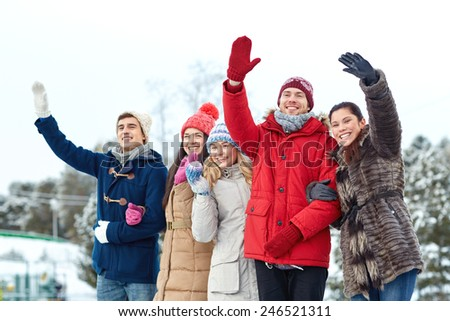 people, winter, friendship, sport and leisure concept - happy friends waving hands on ice rink outdoors - stock photo