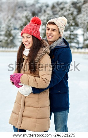 people, winter, love and leisure concept - happy couple hugging ice skating on rink outdoors - stock photo