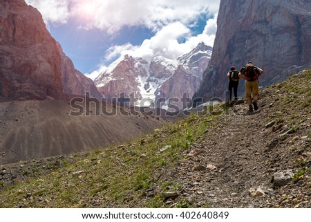 People with Backpacks Walking Up on Rocky Trail along Green Meadow and High Rock Walls and Summits on Background Blue Sky Clouds Sunny - stock photo