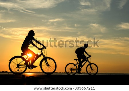 people with bike on the pier at sunset