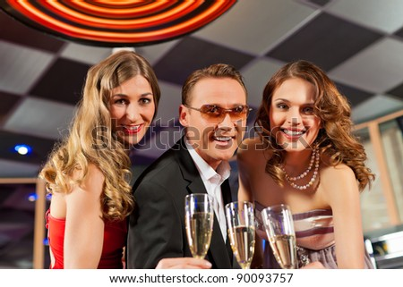 People with champagne in a bar having lots of fun - stock photo