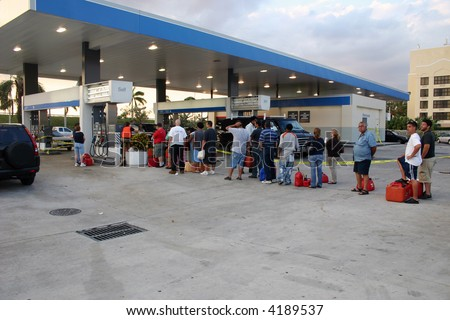 People with empty containers waiting in line to buy gasoline. [NAME BRANDS REMOVED]