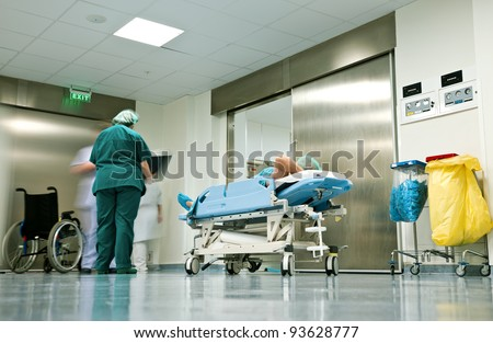 People with medical uniforms and patient lying on trolley in hospital corridor - stock photo
