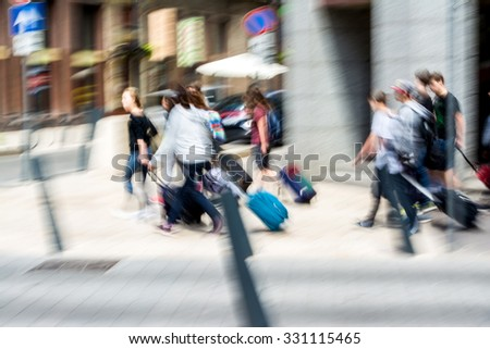 People with suitcases in a hurry on the street of the city. Intentional motion blur