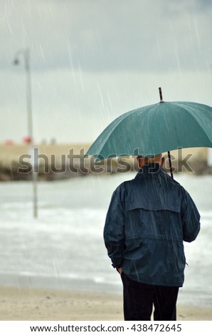 people with umbrella walking under the rain - stock photo
