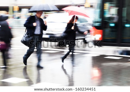 people with umbrellas crossing the wet street - stock photo