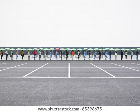 People with umbrellas waiting in line - stock photo