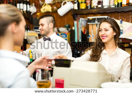 People working in a bar: waitress is taking a check from a cashier while handsome bartender is mixing drinks in background - stock photo