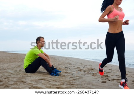 People working out on the beach, seated male runner relax after training and observe how his girlfriend engage the sport outdoors, couple having sports time next to the sea - stock photo
