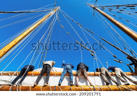People working together to raise a big heavy sail on a tall ship at sea. Concepts: teamwork, cooperation, working toward a common goal, depending on each other - stock photo