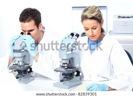 People working with a microscope in laboratory. - stock photo