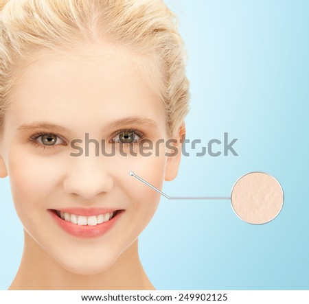 people, youth, skincare and beauty concept - face of beautiful happy teenage girl over blue background - stock photo