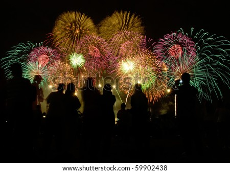 peoples in silhouette enjoy watching firework show - stock photo