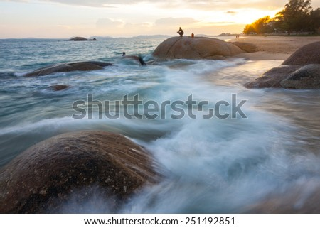 peoples in view of a rocky coast in sunrise - stock photo