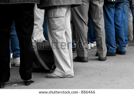 Peoples legs, wearing trousers and jeans. Desaturated with only the jeans saturated.
