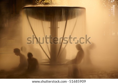 Peoples sitting in fountain in aqua park - stock photo