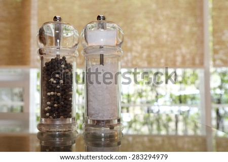 pepper and salt shakers on the wooden table - stock photo