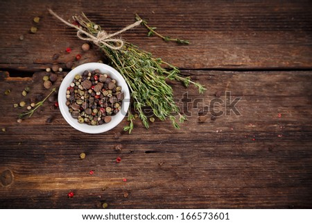 Pepper and thyme on wooden board - stock photo