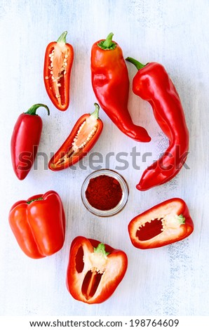 Pepper capsicum chilli paprika family fresh red produce on white rustic background - stock photo