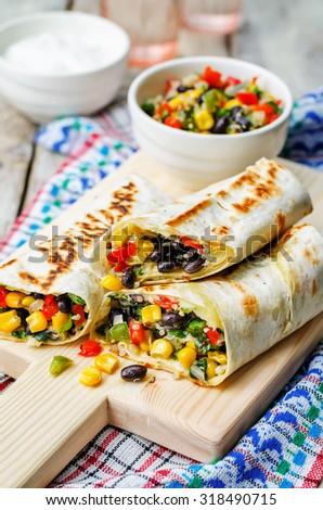 pepper corn black bean quinoa burritos on a white wood background. the toning. selective focus - stock photo