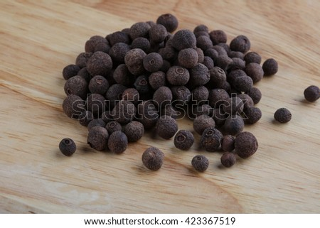 Pepper corn heap on the wood background - stock photo