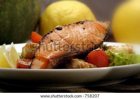 Pepper-crusted Salmon with panzanella and salad. - stock photo