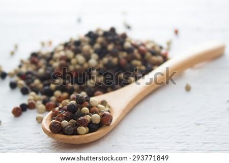 pepper in wooden spoon/ mixture of red pepper, black pepper, white pepper, green pepper - stock photo
