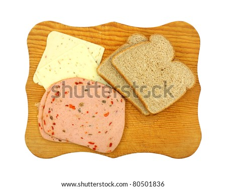 Pepper Jack cheese and pickle pimento luncheon meat with whole wheat bread on a wood cutting board. - stock photo