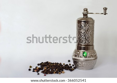 Pepper mill and peppercorn on light background - stock photo