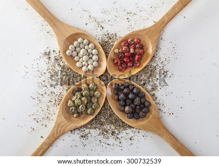 Pepper mill on a white isolated background with peppers green, red, black and white pepper next to the wooden spoon - stock photo