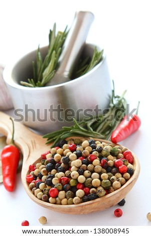 Pepper on wooden spoon, metal mortar with pestle, chinese garlic , herbs and spices over white - stock photo