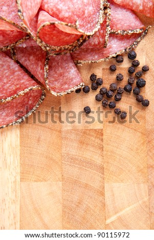 Pepper salami slices and spices on wooden background