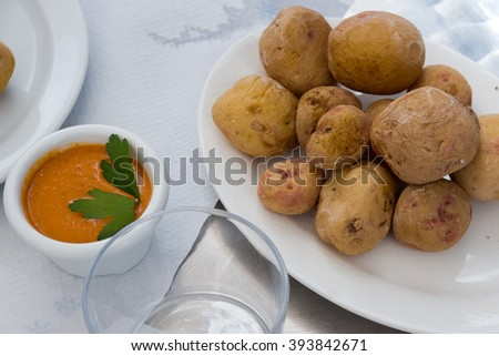 Pepper sauce, canarian wrinkly potatoes at the outdoors restaurant in Lanzarote. Papas Arrugadas - Small new potatoes which are cleaned with peel are usually served with a pepper sauce, called Mojo   - stock photo