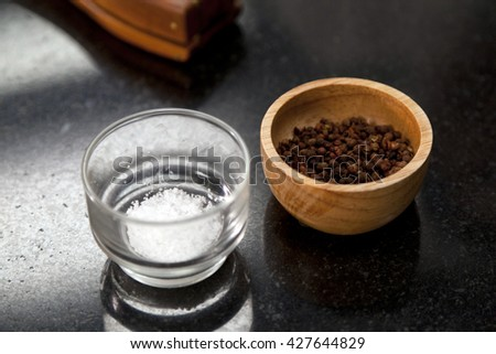 peppercorns and sea salt in a bowl on a dark background - stock photo