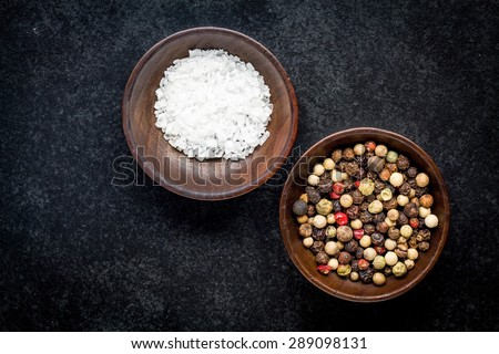 peppercorns and sea salt in a wooden bowl on a dark background - stock photo
