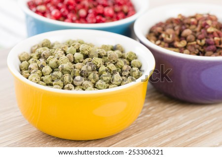 Peppercorns - Green, szechuan and pink dried peppercorns in colourful bowls.