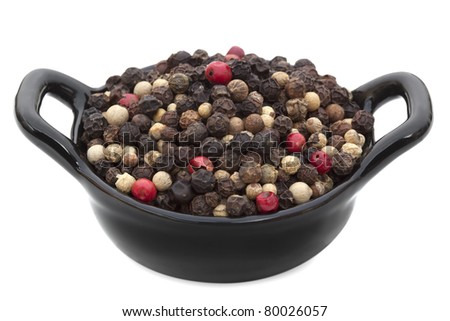 Peppercorns in a small black bowl, isolated on white.
