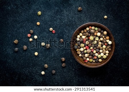 Peppercorns in a wooden bowl on a dark background - stock photo
