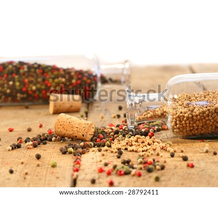 Peppercorns in glass bottles on rustic wood table - stock photo