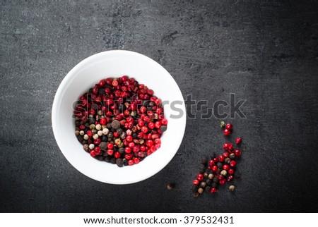 Peppercorns mixed in bawl on dark background. Top view with copy space. - stock photo