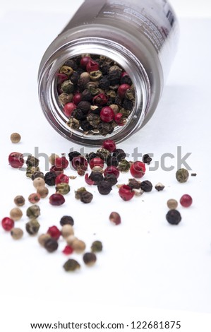 peppercorns spilled on a white background - stock photo