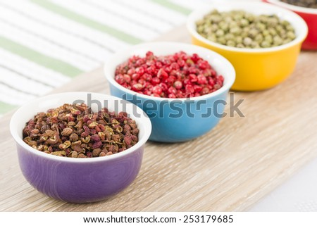 Peppercorns - Szechuan, pink, green and black dried peppercorns in colourful bowls. - stock photo