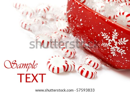 Peppermint candies with holiday snowflake dish on white background with copy space.  Macro with shallow dof.