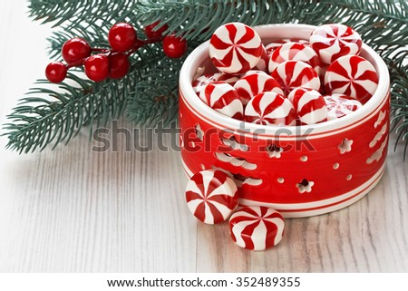Peppermint sweet candy and Christmas decoration with berries and pine branch/Peppermint Christmas candy  - stock photo