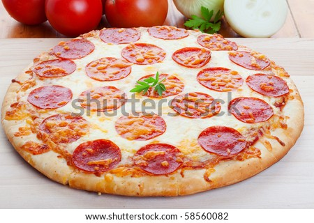 Pepperoni pizza closeup on wood with onions and tomato in the background - stock photo
