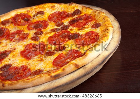 Pepperoni pizza on a wooden plate - stock photo