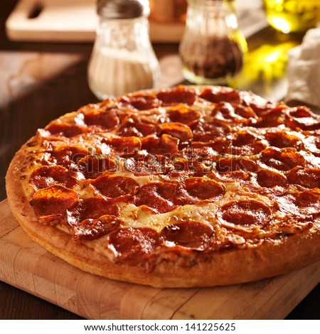 Pepperoni pizza on table - stock photo