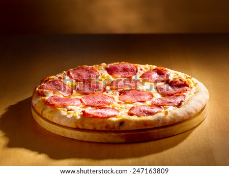 pepperoni pizza on wooden background - stock photo